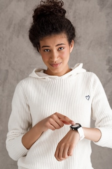 Cute teenage woman pointing at watch, hurry up, no time