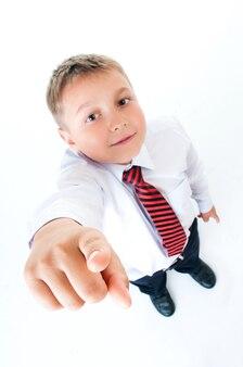 Милый мальчик-подросток в белой школьной рубашке и галстуке, указывая пальцем на белом изолированном фоне.