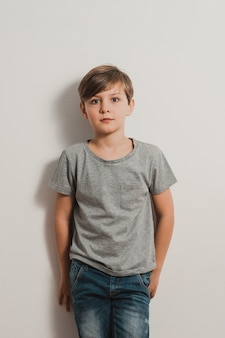 Cute teenager boy stands next to white wall, grey t-shirt, blue jeans, frightened face
