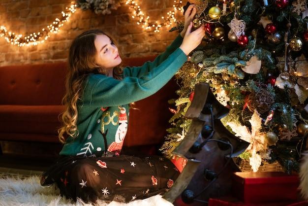 かわいいティーンエイジャーの女の子は、鹿の居心地の良い魔法の緑のセーターの赤いボールでクリスマスツリーを飾ります...