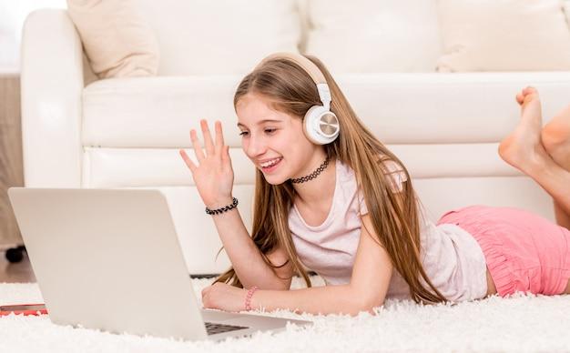 彼女のラップトップで笑っているかわいいティーンエイジャーの女の子