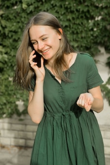Cute teenager girl talking and smiling on mobile phone outdoor