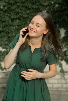 Cute teenager girl talking and smiling on mobilephone