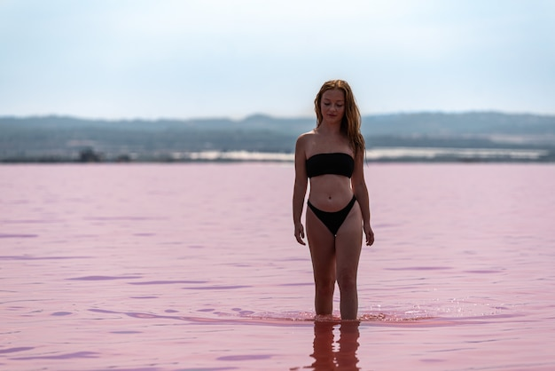 Cute teenager girl in the water of an amazing pink lake