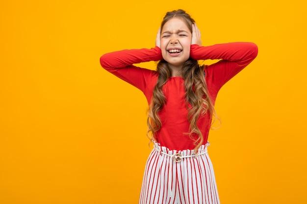 Милая девочка-подросток с вьющимися волосами в красной блузке и полосатых брюках щурилась и закрыла уши на желтом с копией пространства
