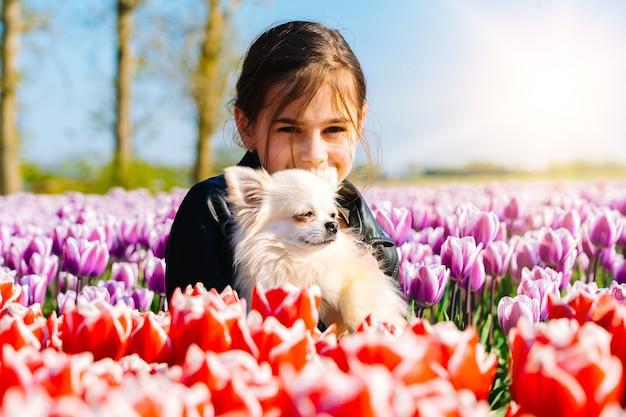 アムステルダム地域のチューリップ畑でチューリップの花の匂いがする長い髪のかわいいティーンエイジャーの女の子