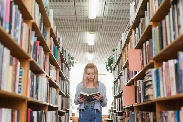 Adolescente sveglio leggendo tra scaffali