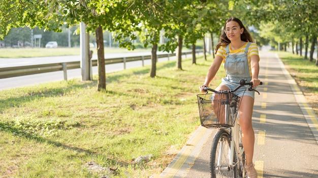 屋外で自転車に乗ってかわいいティーンエイジャー