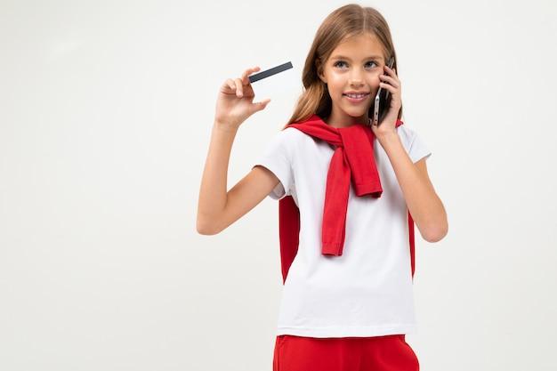 美しい顔でかわいいティーンエイジャーは、クレジットカード、白で隔離される画像を保持しています。