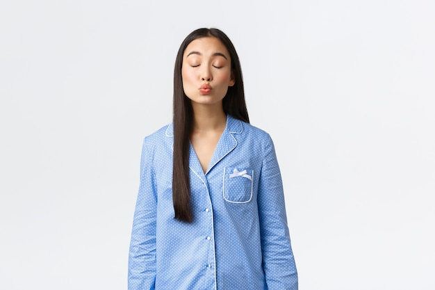 Cute tender asian girl in blue pajamas having romantic dream at night, close eyes and kissing someone, imaging boyfriend or date, standing white background, daydreaming.