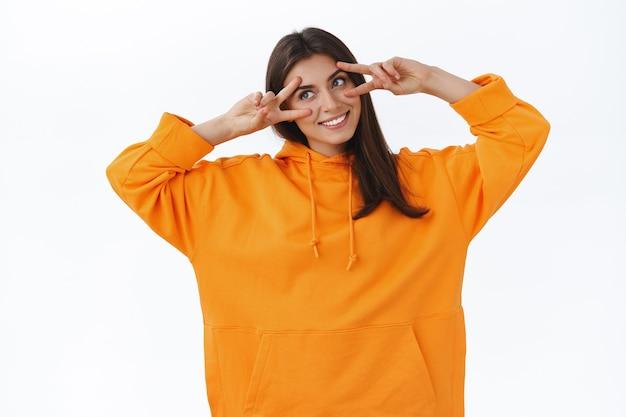 オレンジ色のパーカーを着たかわいい優しい女性の白人女性は、目の上に平和の兆候を示し、頭を傾けて幸せそうに見え、笑顔でポジティブな雰囲気、歓声と喜び、白い壁を広く表現します