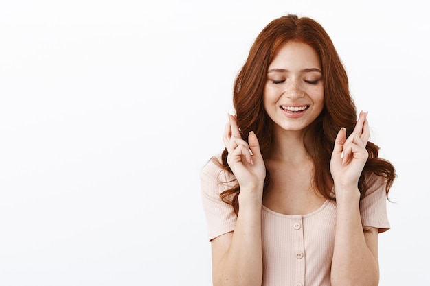 Cute tender and feminine young girl with red curly hair, close eyes romantically smiling, wanna dream come true, cross fingers good luck, making wish, ancitipating miracle hopeful