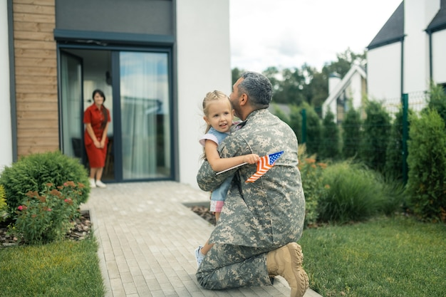 Cute tender girl. military officer feeling memorable hugging his cute tender girl while coming back home