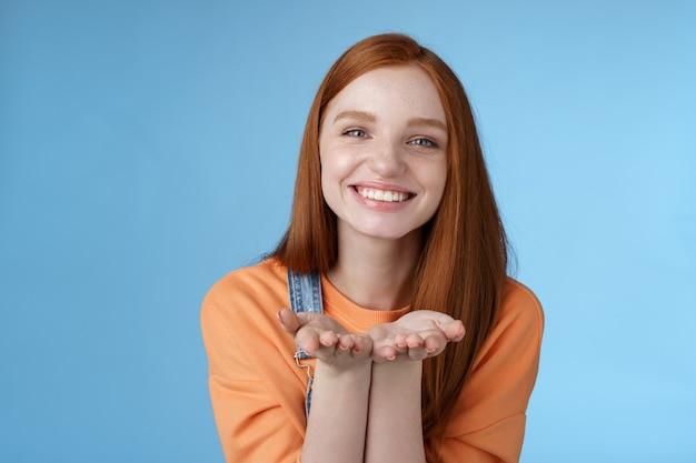 かわいい優しい優しい若い生姜の女の子は、あなたが何かを持っているすべての愛を与える手のひらを見せてカメラの笑顔を喜んで紹介します現在のニヤリとロマンチックなジェスチャーを送信します空気キス青い背景を送信します