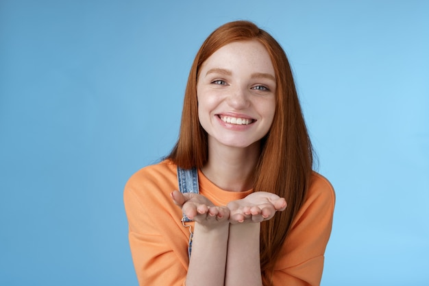 모든 사랑을 주는 귀엽고 친절한 어린 생강 소녀, 카메라를 들고 기뻐하는 모습을 보여주는 손바닥을 들고 현재 웃고 있는 낭만적인 제스처를 소개합니다.