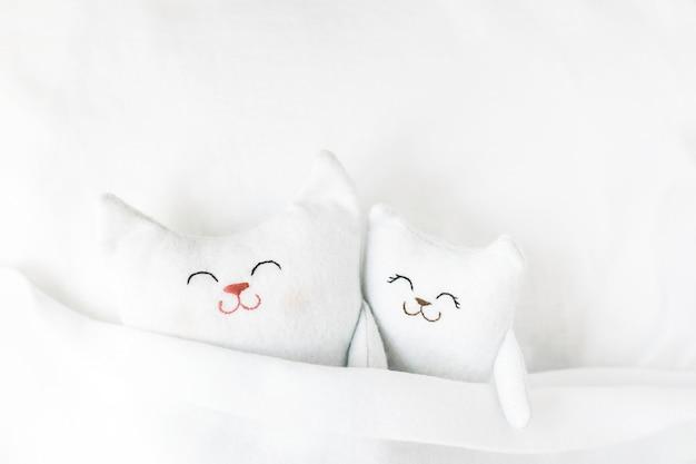 かわいいやわらかい子猫が白い毛布の下のベッドで寝る睡眠の概念快適さの概念