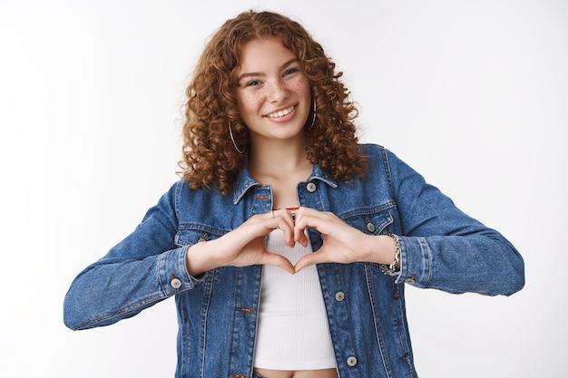 かわいい優しい若い幸せな赤毛の巻き毛の女の子の傾きの頭は喜んでハートサインを表示します強い健康的な関係を気遣う愛の積極性を表現し、同情の情熱を表現し、広くカメラを笑顔