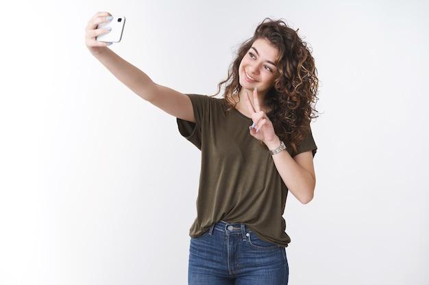 20대 귀엽고 행복한 미소짓는 아르메니아 곱슬머리 소녀가 팔을 뻗어 셀카를 찍는 스마트폰을 들고 평화나 승리의 제스처를 포착하여 온라인에서 친구를 공유합니다.