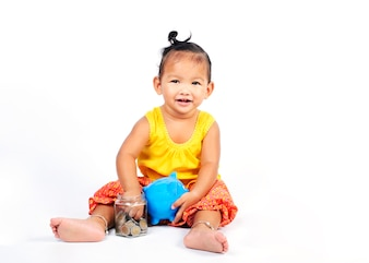 Cute thai baby girl enjoy playing coins and blue piggy bank for finance ideas concept