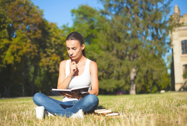 Cute thinking brunette student girl in casual clothes is sitting on the grass and learning some material from  lesson on university background