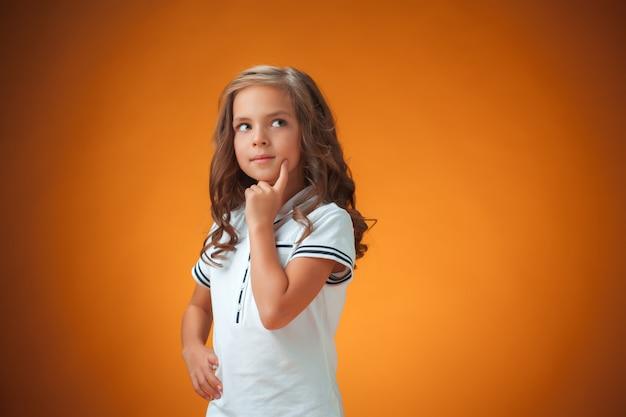 Cute thoughtful little girl on orange