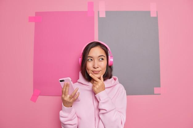 かわいい思慮深い若いブルネットのアジアの女性はあごを保持します何かが携帯電話を保持していると考えています週末を過ごす方法を考えています空白のコピースペースに対してカジュアルな服を着たヘッドフォンで音楽を聴きます