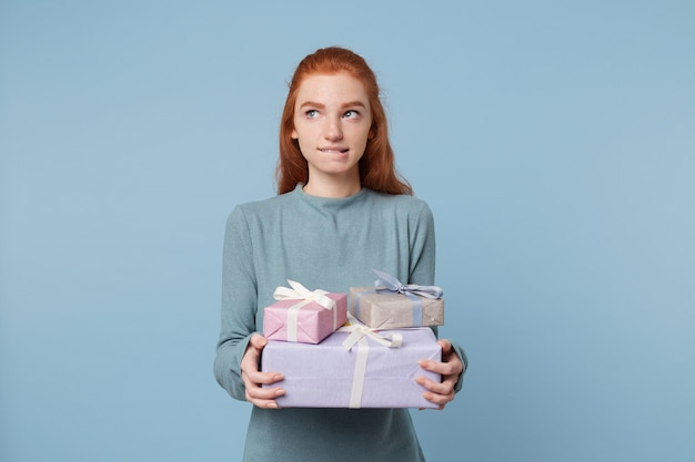 Cute thoughtful young red-haired woman stands holding boxes with gifts, looks away, bites her lip