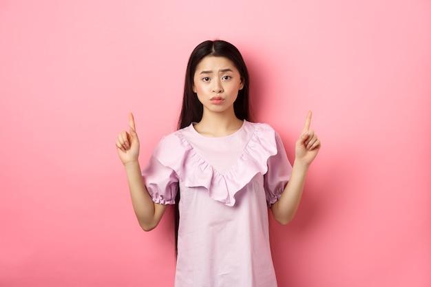 귀여운 겁 많은 아시아 여자 손가락을 가리키는, 인상을 찌푸리고 화가, 로고에서 손가락을 가리키는, 분홍색 배경에 드레스에 서.