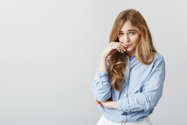 Симпатичная застенчивая студентка в рубашке с синим воротником, держащая руку возле губ и поднимающая брови, делая нежное выражение лица, делая вид, что невиновна