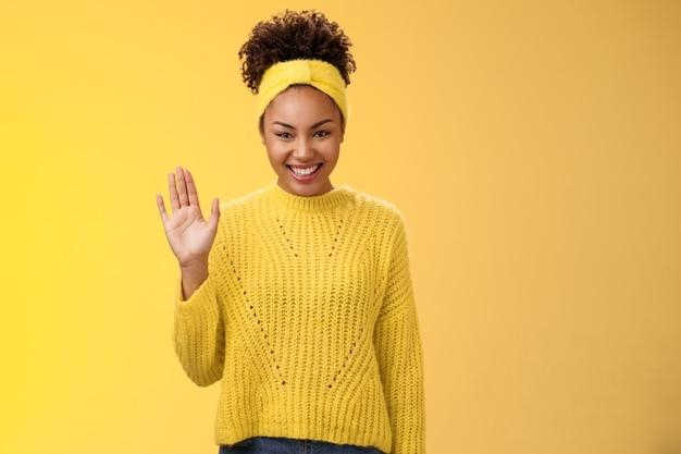 귀여운 소심하고 친절한 어린 소녀는 새로운 친구를 찾고 싶어하며 즐겁게 웃고 매력적으로 기쁘게 손을 흔들며 인사합니다. 인사하는 환영 인사, 노란색 배경.