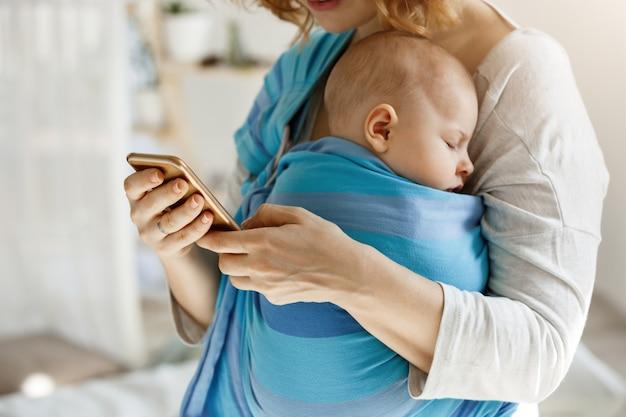 어머니가 그를 포옹하고 전화로 문자 메시지 남편에게 아기 음식과 기저귀를 사면서 평화롭게 낮잠을자는 귀여운 작은 아이. 라이프 스타일, 가족 개념.