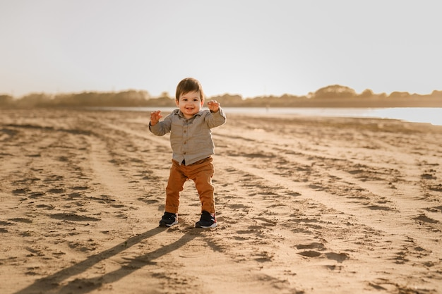 Милый мальчик малыша, идущий на песчаном пляже.