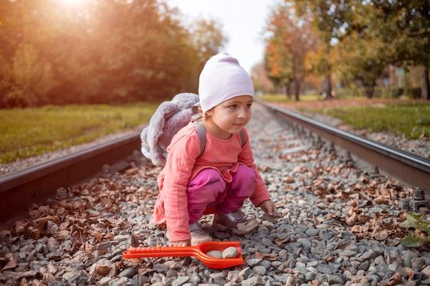 귀여운 유아 아기 소녀는 혼자 철도 트랙에 앉는다. 위험 개념입니다.