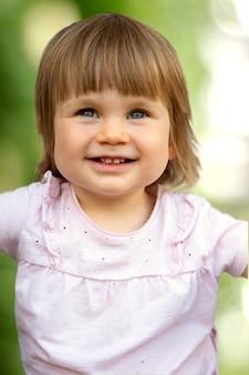 Милый малыш, ребенок улыбается на размытом зеленом фоне. красивая маленькая девочка с удовольствием.