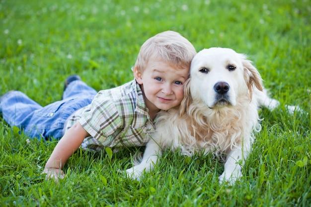 ゴールデンレトリバーを抱き締めてかわいい幼児の金髪の少年