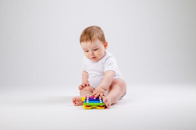 Милый малыш мальчик 8 месяцев в белом боди играет с развивающей игрушкой сидя