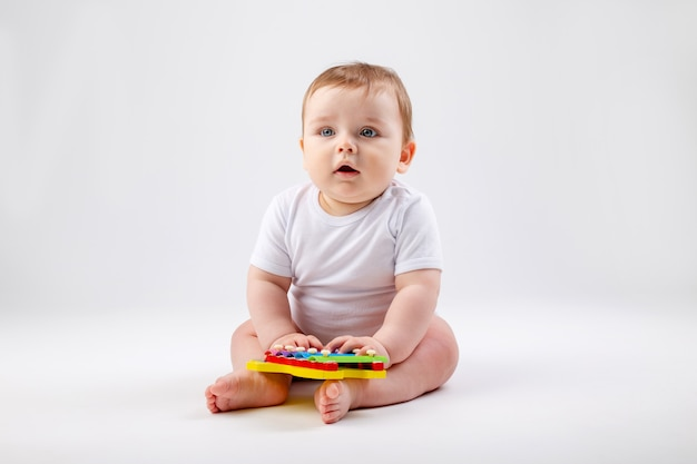Cute toddler boy 8 months old in white bodysuit plays with developing toy sitting