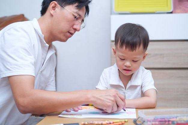 Cute toddler boy child painting with crayons kid coloring with father at home