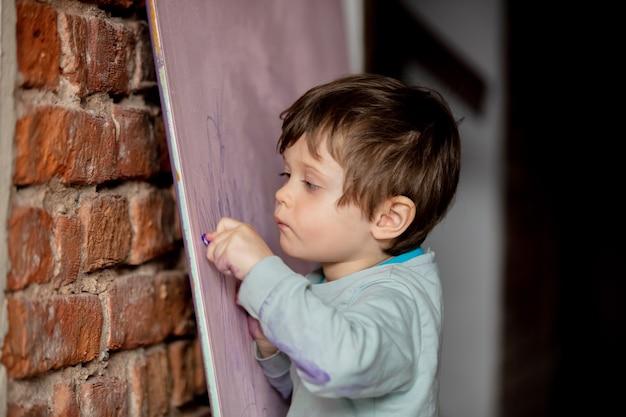 집에서 패널에 그림을 그리는 귀여운 유아 소년. 측면보기