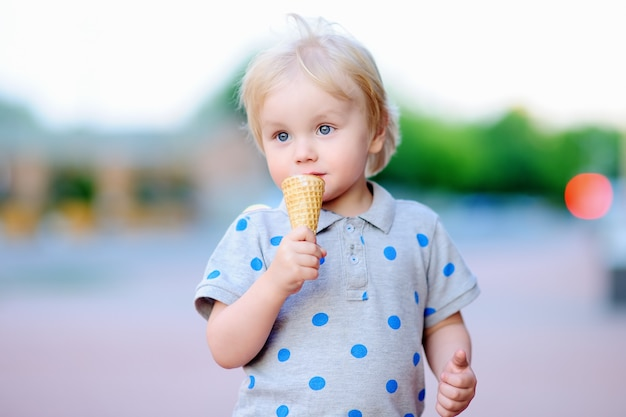 Cute toddler boy eating ice-cream outdoors