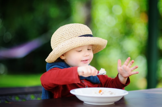 야외에서 쌀 시리얼을 먹는 귀여운 유아 소년. 어린 아이들을위한 건강에 좋은 음식