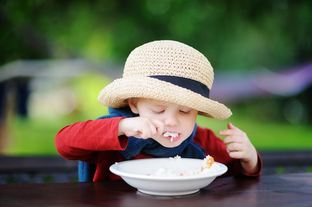 Cute toddler boy eating rice cereal outdoors. healthy food for little kids