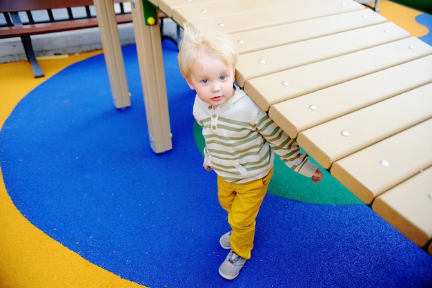 Cute toddler boy having fun on playground.