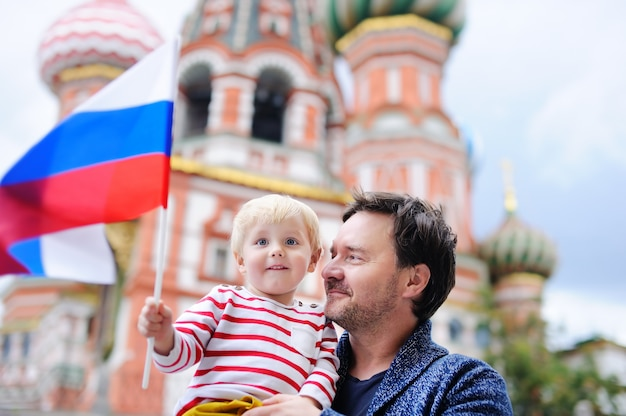 Cute toddler boy and his middle age father holding russian flag with saint basil's cathedral