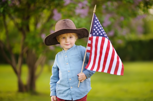 Cute toddler boy holding american flag in beautiful park.