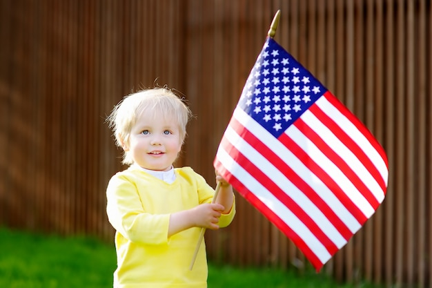 Cute toddler boy holding american flag.