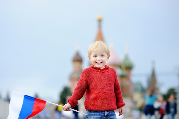 Cute toddler boy holding russian flag with red square and vasilevsky descent
