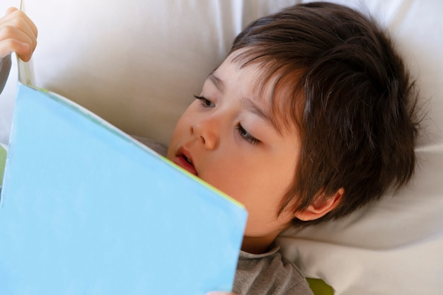 Cute toddler boy laying in bed readinga book before he goes to sleep