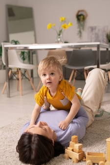 Cute toddler boy lying on mothers chest and looking up while they playing on floor at home