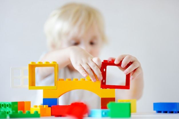 Cute toddler boy playing with colorful plastic blocks indoors, focus on hands